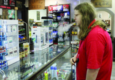 """<div class=""""source""""></div><div class=""""image-desc"""">Juul e-cigarette starter kits and replacement pods are on prominent display at Tobacco Mart and other retailers around Grant County. John Fischer, right, smokes his Juul while browsing at Tobacco Mart. Photos by Amanda Kelly</div><div class=""""buy-pic""""><a href=""""/photo_select/32195"""">Buy this photo</a></div>"""