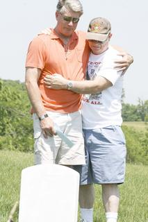 Ken Densler, of Florida, stands with his uncle, Danny Densler, of Latonia, at his father's grave.