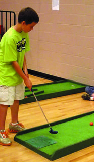 Matthew Grubbs gives golf a try during SES's track and field day.