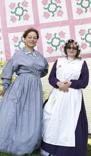 Sharon Plummer and Tonya Lawrence stand in front of hand-sewn quilts. Plummer, a member of the historical society made their 1800s era dresses.
