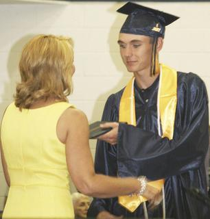Asst. Superintendent Jennifer Wright presents her son, Zachary Wright, with his diploma.
