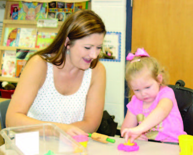 CMZ preschool Amanda Newman helps Adalynn Rarrieck with her Playdoh creation.