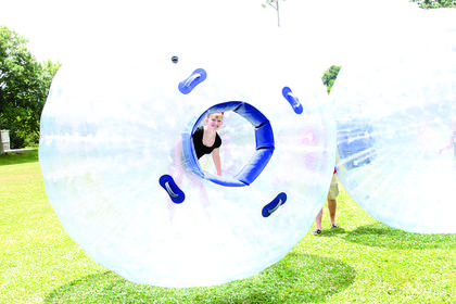 Alexis Faust peeks out from inside a giant hamster ball.