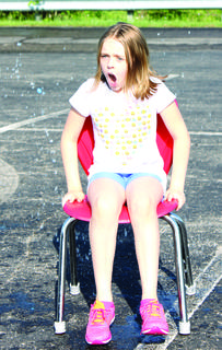 MCE's Alexis Hall reacts to cold water after popping a water ballon in the chair during a relay race at track and field day May 23.