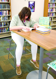 Ava Herrmann reads a book at one of the new tables set up at the library.