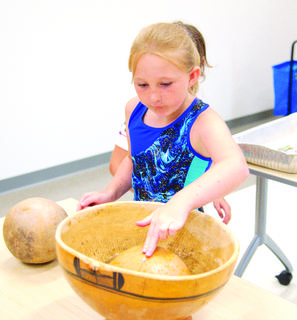 Brianna Webster plays a water drum of African origin.