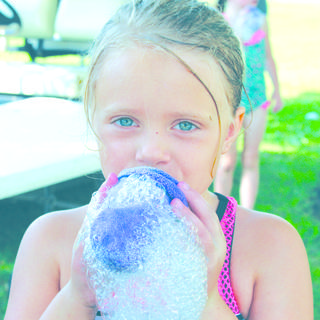 Brylee Dills blows bubbles with her handmade toy.