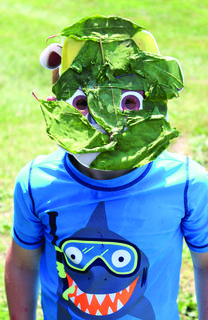 Caid Yates shows off the mask he made with fallen tree leaves.