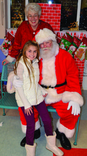 Carlee Manning poses for a quick photo with Santa Claus and Mrs. Claus at SES.