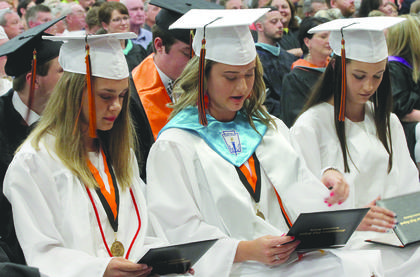 Carlee Slaughter, Morgan Thompson and Mavis Williams check out their diplomas after walking across the stage at graduation May 25.