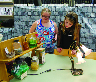 Chloe Hutchinson and June Lilly look through the potions and ingredients to see if one is a clue.