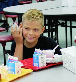 """CMZ student Bryson Fornash pretends his empty juice cup is a phone while playing """"Telephone"""" after lunch."""