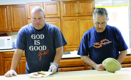 Darryl Cummins and Tom Beach take a moment to pray while serving plates of pancakes, bacon, eggs and sausage during the prayer breakfast.