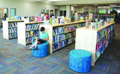 David Chadwick focuses on reading his book on one of the new chairs in the children's section of the library.