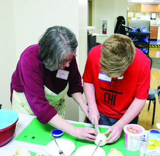 Grant County Extension Homemakers member Cindy Briggs guides  SES student Dillon Baker cut an onion for broccoli spoonbread.