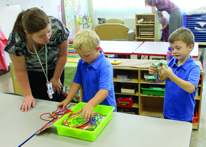 DRE preschool aid Amanda Scott helps Jayden Harper and Bentley Webster untangle strings in a toy box.