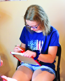 Riley Conrad, left, and Danika King, center, consider what to draw during Vacation Bible School at Knoxville Baptist.