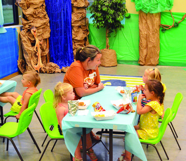 Izzy Coleman, left, takes a break for a snack while Lindsay Wynn, center, talks with a group of children.