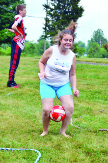 Kiersten Beighle, left, and Austin Beighle, center, run a relay holding a ball between their knees.