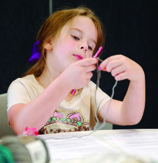 Abigail Miller concentrates on her needle and yarn.