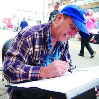 'Two-handed Mikey', a caricature artist, draws an attendee.