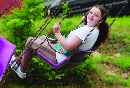 Gabby MacAdams flies around on a swing at the small carnival at the festival.