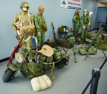 Military artifact displays line the room at the museum located next to Uncle Leroy's General Store.