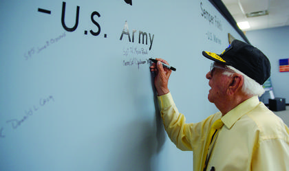 """Julian Wills signs his name next to fellow Army veterans on the museum's  """"guest wall."""""""