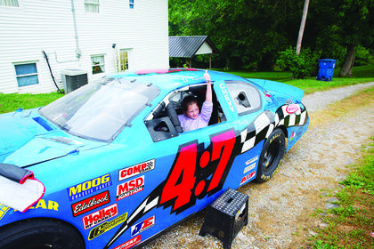 Maci Fox gives a thumbs up while inside the race car.