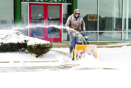 A property manager at Dry Ridge Towne Center clears off a pathway for visitors.