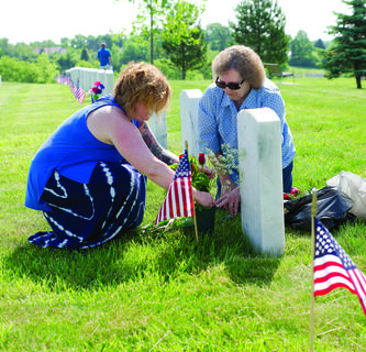 Amber and Marty Updike lay flowers at Andrew Updike's grave during a Memorial Day event. Photos by Mark Verbeck