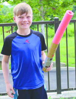 Gage Nix is all smiles as he holds the finished product of his DIY pool noodle lightsaber.