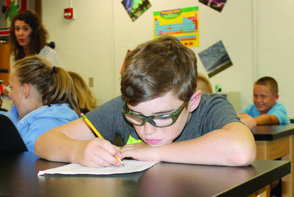 GCMS student Brett Mann doodles on his class schedule at the end of the school day for sixth graders.