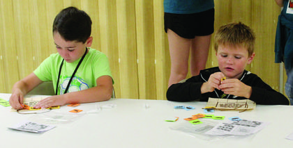 Gideon Hayhoe and Kaddesh Opperman place animal stickers on their Bible verse art project during VBS.