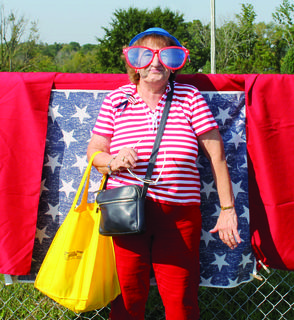 Pat Stivers poses for a photo decked out in patriotic props.