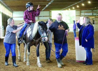Joseph Kelley waves while riding a horse around the stable with the help of teacher Diana Barker. Photos by Amanda Kelly