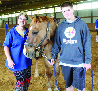 Amanda Bass and a Lovesome Stables volunteer hang out in the stable.