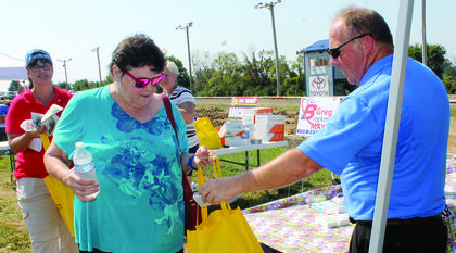 Margaret Ryan, above, gets freebies from realtor Jim Morris. Hundreds of local seniors attended Senior Bash 2018 despite the hot, humid weather. See more photos on page 2. Photos by Amanda Kelly
