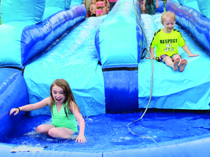 Cassidee Jackson reacts to the chilly water after sliding down the lane with her brother, Cayden Jackson.