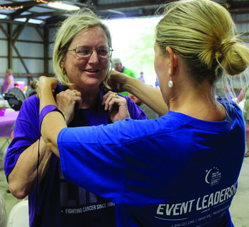 Mattie Gutman places a medal around Brenda Simpson's neck during the annual Grant County Relay for Life at Grant County Park.