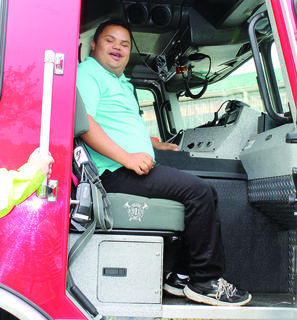 Patrick Donato sits in the captain's seat in a fire truck during the event.