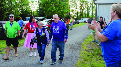 Survivors are applauded while completing their first lap around the cattle barn to kick off this year's event. Photos by Amanda Kelly