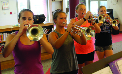 Emily Durbin, Tori Hagedorn, Liberty Palmer and Terah Leap blare their horns as they practice playing loud.