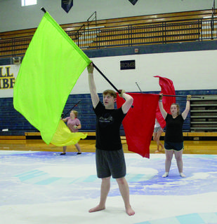Logan Klette shows Serena Epperson how to execute a pop toss with their practice flags for color guard.