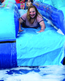 Olivia Brewster flies down her lane after park employees add more soap to the slide during Grant County Parks and Recreation's Kick Off to Summer event June 14.