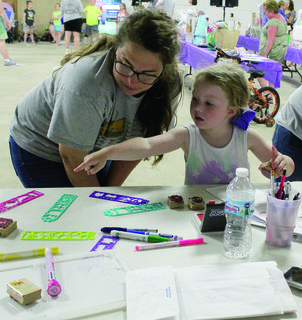 Lillian Dale points to what stencil she wants to use to decorate her Luminaria bag while Jessica Smith helps her.