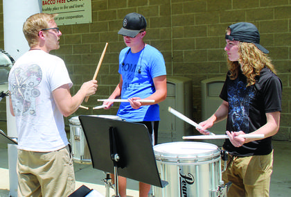 Percussion instructor Jayson Smith helps Zach Williams and Hunter Manning learn their measures.