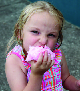 KICKING OFF THE SUMMER –  Aubree Beers chows down on some cotton candy after playing on the slip 'n' slide at Grant County Park's June 14 Summer Kickoff event. See more photos on page 20. Photo by Amanda Kelly