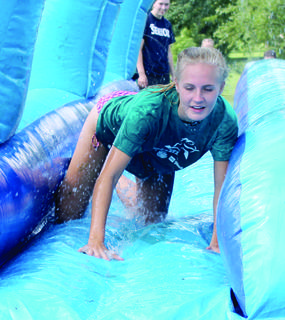 Volunteer Shelby Gutman, above right, shows the younger campers how it's done on the slide.