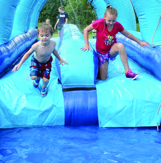 Xavier Carr and Cameron Clark, right, get to the end of the slip 'n' slide before hopping into a pool on the last day of Little Dippers summer camp June 28.